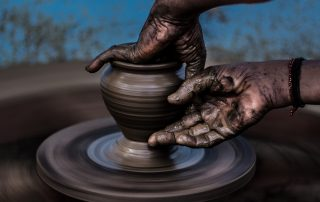 two hands sculpting clay on a potter's wheel