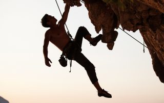 silhouette of a man climbing