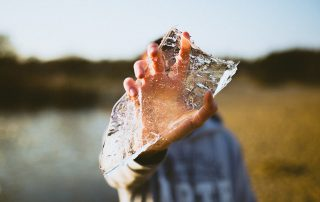a picture of a person's hand holding a shard of ice