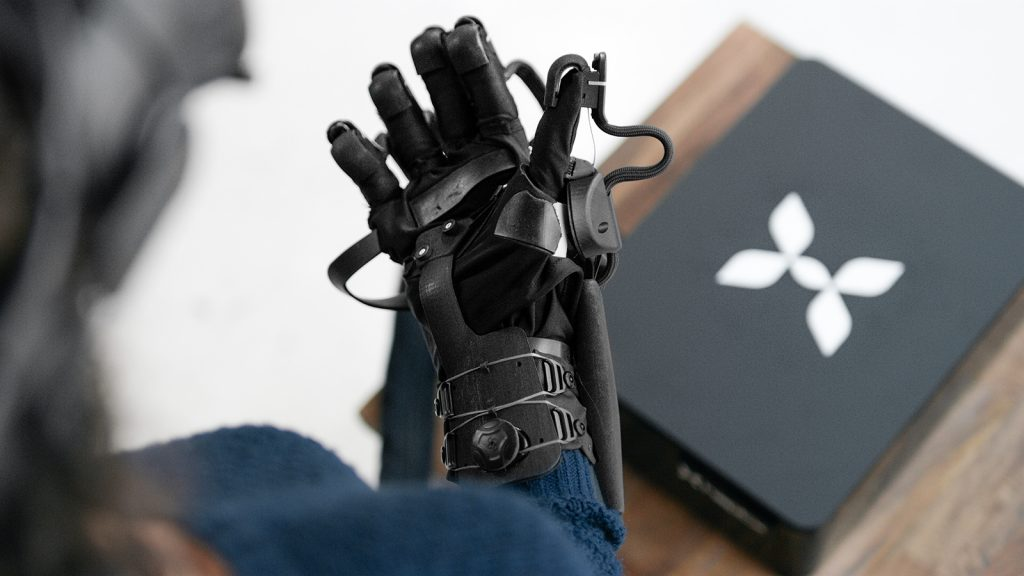 a woman looking down at the haptx glove and console