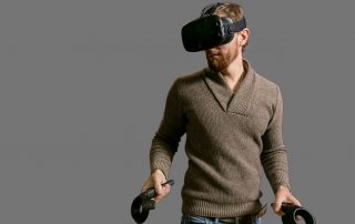a bearded man in a sweater using an HTC vive